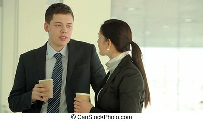 Coffee break - Two businesspeople drinking coffee and...