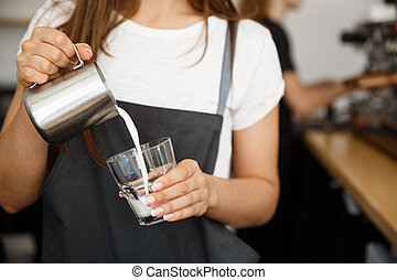 Coffee Business Concept - close-up lady barista in apron preparing and pouring milk in glass cup while standing at cafe.