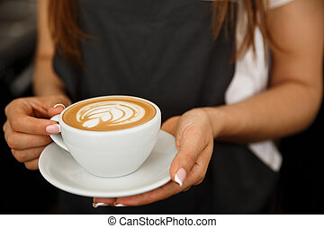 Coffee Business Concept - Cropped Close up of female serving coffee with latte art while standing in coffee shop. Focus on female hands placing a cup of coffee.