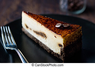 Coffee Cheesecake on Black Plate with Dark Wooden Surface.