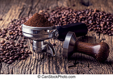 Coffee. Coffee beans and portafilter on old oak wooden table