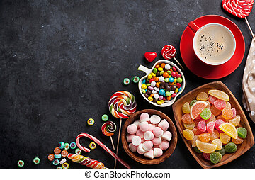 Coffee, colorful candies, jelly and marmalade on stone background. Top view with copy space
