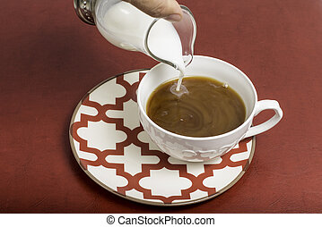 A coffee mug that has creamer being poured in.