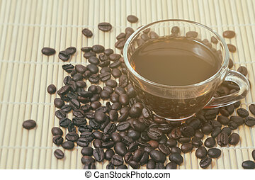 Coffee cup and beans on wooden background.
