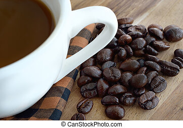 Coffee cup and beans on wooden
