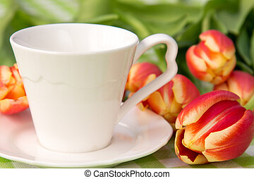 Coffee cup and bunch of tulips