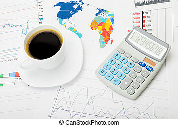 Coffee cup and calculator over world map and stock market charts