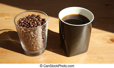 Coffee cup and coffee beans - A hot steaming coffee cup with...
