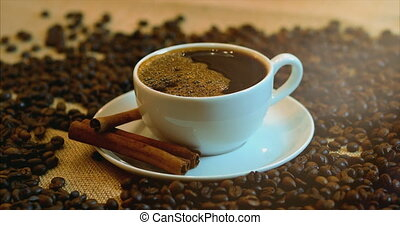 Coffee cup and coffee beans. A white cup of evaporating coffee on the table with roasted bean. Stock footage 4k.