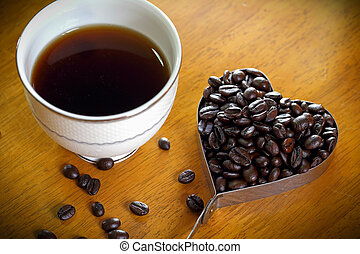 coffee cup and Coffee Beans heart shape on wooden table