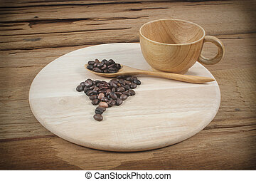 Coffee cup and coffee beans on wood board isolated