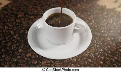 Coffee cup and coffee beans. White cup of evaporating coffee on the table with roasted bean. Stock footage 4k.