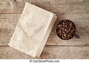 Coffee cup and coffee beans with old book