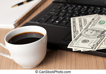 coffee cup and computer with money