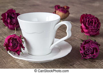 Coffee cup and dry buds of roses