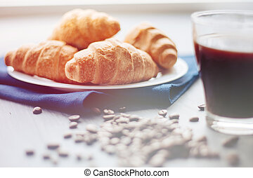 Coffee cup and fresh baked croissants on wooden background. Top , light toning