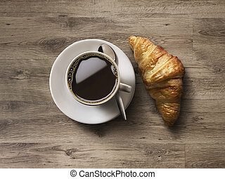 Coffee cup and fresh baked croissants on wooden background.
