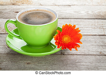 Coffee cup and gerbera flower on wooden table
