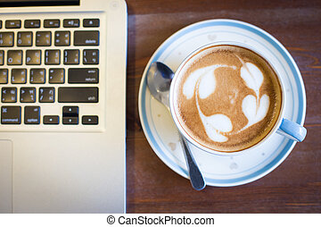Coffee cup and laptop on table background
