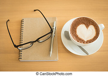 Coffee cup and notebook on grunge wooden background.