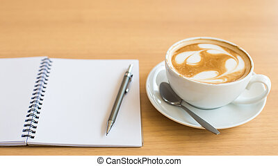 Coffee cup and notebook on grunge wooden background