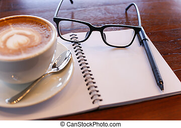 Coffee cup and notebook on table background. - Coffee cup...