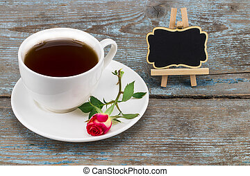 coffee cup and red rose with blackboard with empty space for a text over wooden background