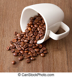 Coffee cup and spilled coffee beans on wood