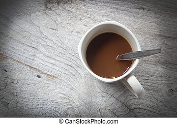 Coffee cup and spoon on wooden background.