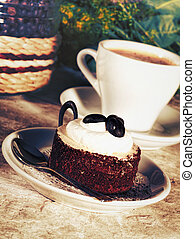 Coffee cup and tasty cake on the desk, food still life for your design