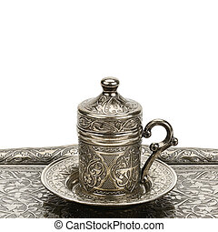 Coffee cup and tray with arabic decoration with metal cup and dish isolated on a white background. Free space for text.