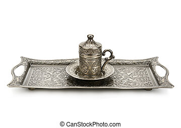 Coffee cup and tray with arabic decoration with metal cup and dish isolated on a white background.