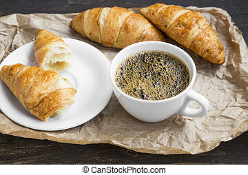 Coffee cup breakfast setting with croissants