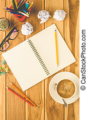 coffee cup, chart, pen, notebook and accessory for work on wooden table.