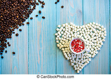 Coffee cup full of candies flat lay on rustic light blue wooden background. Heart figure made from Marshmallows. beans top left corner