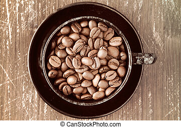 Coffee cup full of coffee beans.