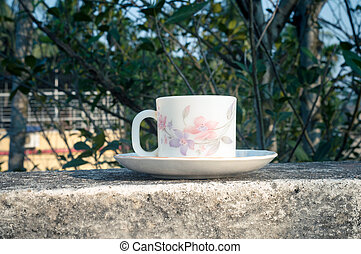 Coffee cup in morning sunlight. Summer fresh cool look. White coffee cup on saucer for hot drink on roof beam of a residential building with bokeh background.