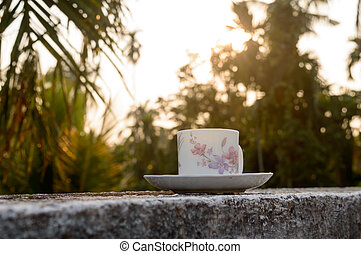 Coffee cup in sunset sunlight. Summer fresh cool look. White coffee cup on saucer for hot drink on roof beam of a residential building with bokeh city in the background.