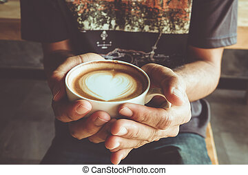 Morning coffee, hands holding cup of hot coffee latte cappuccino with heart shaped foam