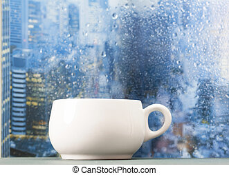 Coffee cup on a rainy day in front of the window