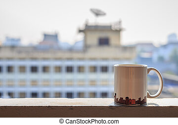 Coffee cup on balcony and blurred view of building