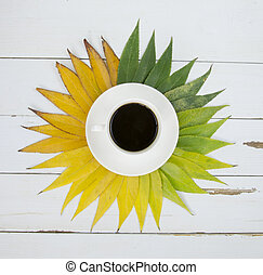 Coffee cup on green yellow leaves background Flat lay.