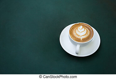 Coffee cup on table with green background