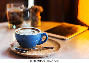 Coffee cup on table with tablet in cafe shop.