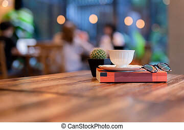 Coffee cup on top of reading book with eyes glasses on table in cafe.