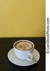 Coffee cup on wooden board with yellow wall as background