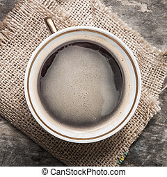 Coffee cup on wooden table texture.