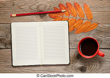 Coffee cup, open diary, pencil and autumn leaves on wooden background