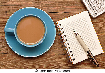 Coffee cup, spiral notebook and pen on the old wooden table