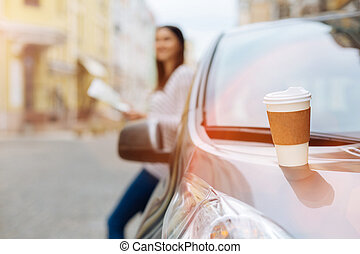 Coffee cup standing on the hood of the vehicle